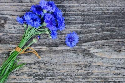 Cornflower blue flowers (Centaurea cyanus) on an old wooden tabl