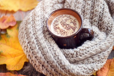 Autumn leaves, hot cup of coffee and a warm scarf on wooden tabl