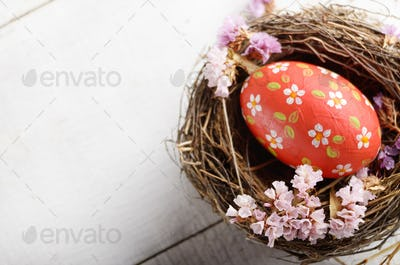 Rustic style painted red easter egg in the nest on white table