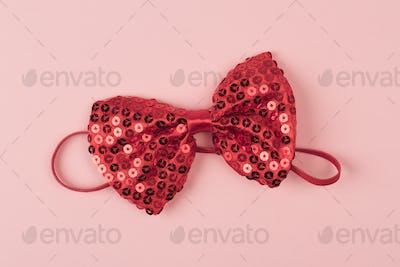 red bow tie with spangles on light pink background