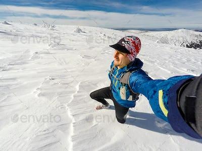 Trail runner selfie in winter mountains