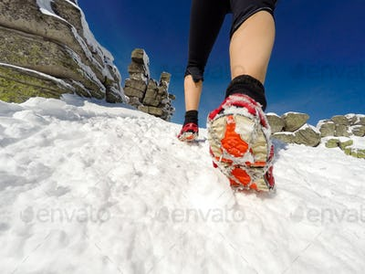 Running woman on winter trail, snow and white mountains