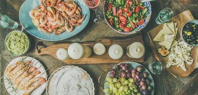 Flat-lay of salad, shrimps, olive, grape, cake, wide composition
