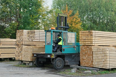 Forklift transports the boards at the plant for woodworking. Woodworking industry