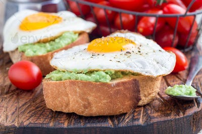Open sandwiches with mashed avocado and fried egg on bread, horizontal