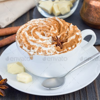Hot white chocolate, decorated with whipped cream and cinnamon, square format