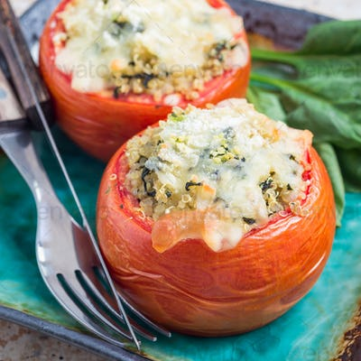 Baked tomatoes stuffed with quinoa and spinach topped with melted cheese, square format