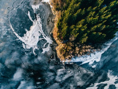 Aerial view of the winter snow forest and frozen lake from above captured with a drone in Finland.