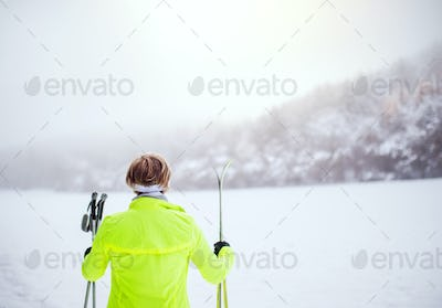Senior woman going cross-country skiing.