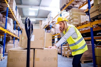 Woman warehouse worker with a smartphone.