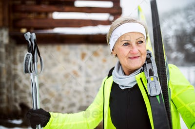 Senior woman getting ready for cross-country skiing.