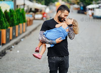 Cute little girl's sleeping in her father's arm