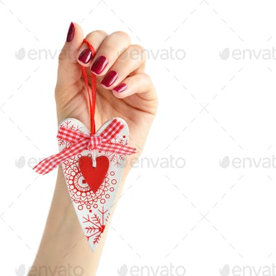 Heart handmade in hand of girl with red manicure on white backgr