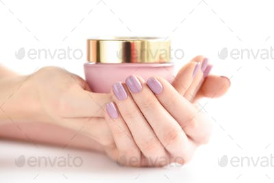 Hands of a woman with pink manicure with jar of cream on white b