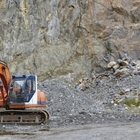 Quarry aggregate with heavy duty machinery. Construction industry. Horizontal