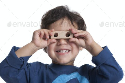 Two year old boy looking through the holes of a block