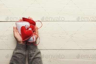 Valentine day background, pillow hearts in female hands