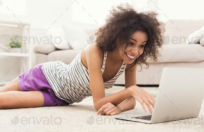 Happy girl with laptop lying on floor