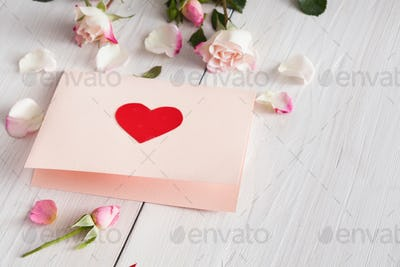 Pink rose flowers and handmade paper card with heart on white rustic wood