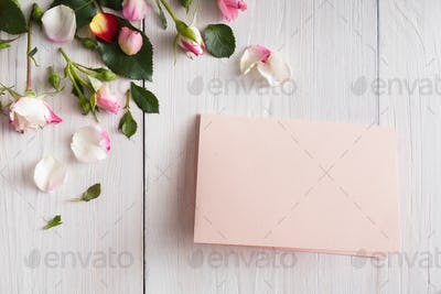 Pink rose flowers petals and handmade paper card on white rustic wood