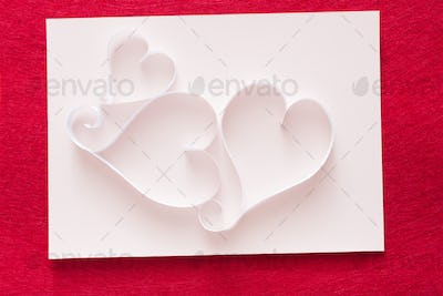 Valentine background with handmade paper heart shapes decoration on white shit of paper on red felt