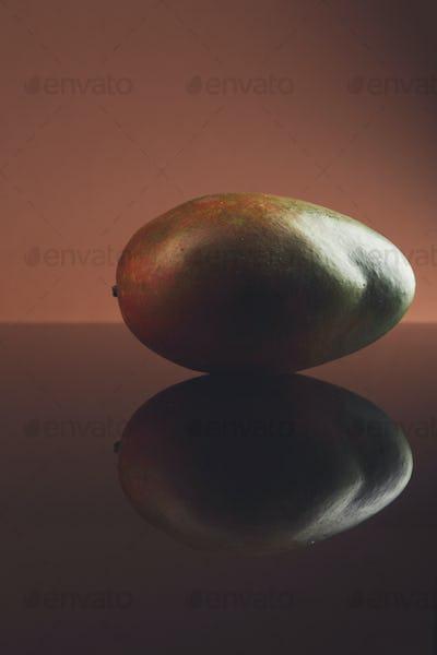 Ripe mango on dark glass background with reflection