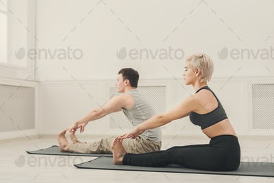 Fitness couple stretching at white background
