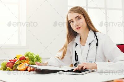 Female nutritionist working on digital tablet