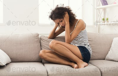 Sad african-american woman on couch at home