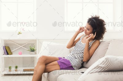 Happy young woman in headphones on beige couch