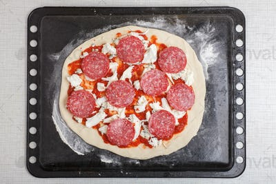 pizza with tomato sauce, pepperoni, cheese on baking tray