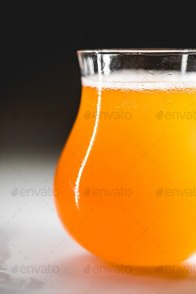 Close-up glass of homebrewed rhubarb beer with white foam.
