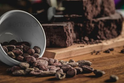 Arrangement of cocoa beans and chocolate bars on wooden surface.