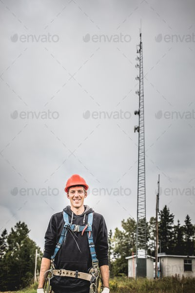 Cheerful young technician in hardhat and harness