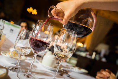 Hand pouring red wine to glass