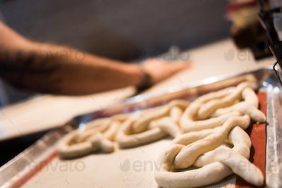 Crop unrecognizable person preparing pretzels.