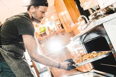 Man taking pan with pretzels
