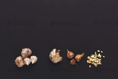 Whole and cut garlic on black isolated background