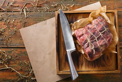 Raw aged prime black angus beef in craft papper on rustic wood