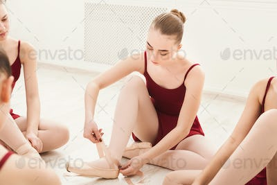 Young girls put on pointe shoes in studio