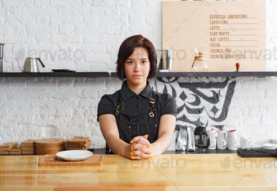 Portrait of young barista at coffee shop counter