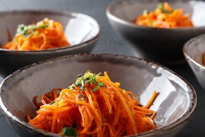 Set of plates with russian korean salad, closeup