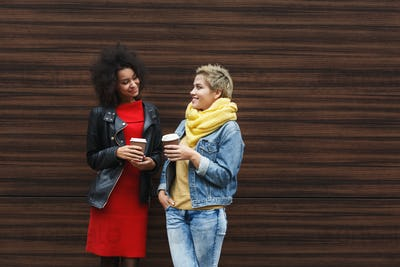 Happy girls with take away coffee outdoors