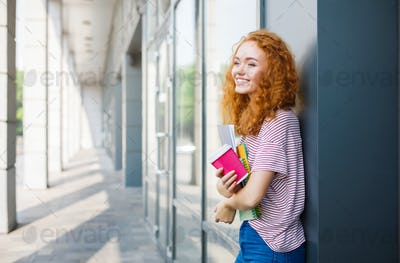 Young smiling redhead student girl with cup of coffee and books