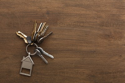 Bunch of keys with house shaped keychain on white wood