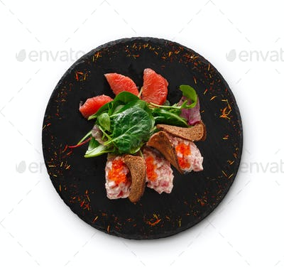 Gourmet seafood snack on black plate isolated
