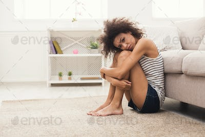 Sad african-american woman on floor at home