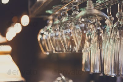 Glasses hanging on bar rack close up