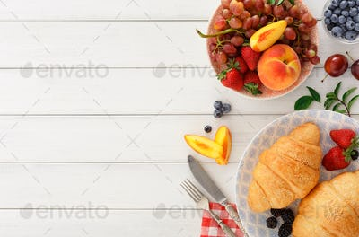Continental breakfast with croissants and berries on white wood