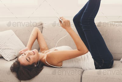 Online. Girl listening to music on smartphone
